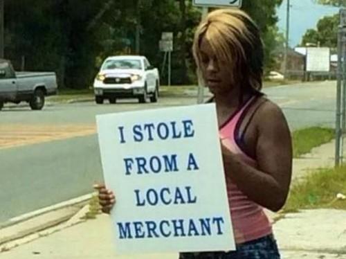 Mulher condenada a segurar placa Eu roubei um comerciante local